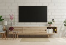 Mockup a TV in modern living room with armchair and plant on brick wall.